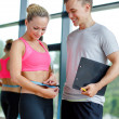 Smiling young woman with personal trainer in gym — Stock Photo #50742293