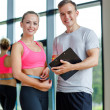 Smiling young woman with personal trainer in gym — Stock Photo #50742415