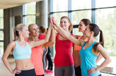 Group of women making high five gesture in gym — Stockfoto