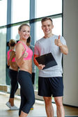 Smiling young woman with personal trainer in gym — Stock Photo