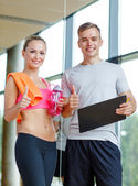 Smiling young woman with personal trainer in gym — Stockfoto