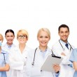 Smiling doctors and nurses with tablet pc — Stock Photo