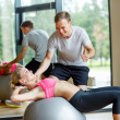 Smiling young woman with personal trainer in gym — Stock Photo #50814821