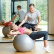 Smiling young woman with personal trainer in gym — Stock Photo #50814867