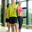 Smiling man and woman showing thumbs up in gym — Stock Photo #50815985