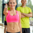 Smiling man and woman showing thumbs up in gym — Stock Photo #50816189