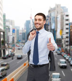 Smiling young businessman showing thumbs up — Foto de Stock