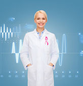 Smiling female doctor with cancer awareness ribbon — Stock Photo