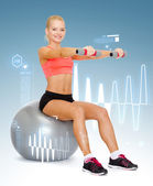 Woman with dumbbells sitting on fitness ball — Stock Photo