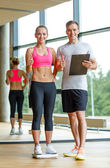 Smiling man and woman with scales in gym — Stock Photo