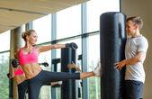 Donna sorridente con personal trainer in palestra di boxe — Foto Stock