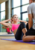 Smiling woman with male trainer exercising in gym — Stock Photo