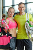 Smiling couple with water bottles in gym — Zdjęcie stockowe