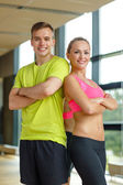 Smiling man and woman in gym — Stock Photo
