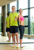 Smiling man and woman showing thumbs up in gym — Stock Photo