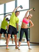 Ler man och kvinna med hantlar i gym — Stockfoto