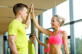 Smiling man and woman making high five in gym — Stok fotoğraf