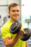 Smiling man with dumbbell in gym — Stock Photo