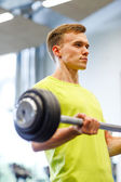 Man doing exercise with barbell in gym — Stock Photo