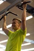 Smiling man exercising in gym — Stock Photo