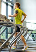 Man with smartphone exercising on treadmill in gym — Stockfoto