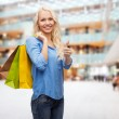 Smiling woman with shopping bags showing thumbs up — Stock Photo #50899751