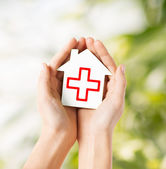 Hands holding paper house with red cross — Stok fotoğraf