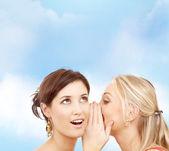 Två leende kvinnor viskar skvaller — Stockfoto