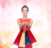 Smiling elegant woman in dress with shopping bags — Stock Photo