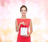 Smiling elegant woman in dress with shopping bag — Stock Photo