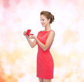 Smiling young woman in red dress with gift box — Stock Photo