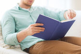 Close up of man reading book at home — Stock Photo