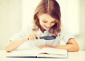 Girl reading book with magnifier at school — Stock Photo