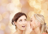 Two smiling young women whispering gossip — Stock Photo