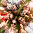 Smiling friends showing thumbs up lying on grass — Stock Photo #50991811