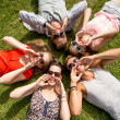 Group of smiling friends lying on grass outdoors — Stock Photo #50991813