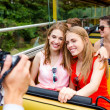 Smiling friends with camera traveling by tour bus — Stock Photo #50993097