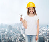Smiling little girl in hardhat with wrench — Stock Photo