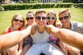 Group of smiling friends making selfie in park — Stock Photo