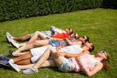 Group of smiling friends lying on grass outdoors — Stock Photo