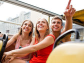 Group of smiling friends traveling by tour bus — Foto Stock