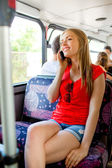 Smiling teenage girl with smartphone going by bus — Stock Photo