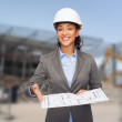 Businesswoman in white helmet with blueprint — Stock Photo #51133401