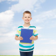 Smiling little student boy with blue book — Stock Photo #51136551