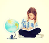 Girl with globe and book — Stock Photo