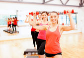 Group of smiling female with dumbbells and step — Stock Photo