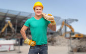 Smiling manual worker in helmet with wooden boards — Stock Photo