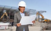 Businesswoman in white helmet with blueprint — Stock Photo