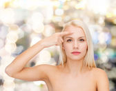 Beautiful woman touching her forehead — Stock Photo