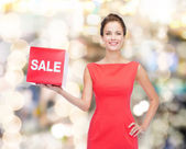 Smiling young woman in dress with red sale sign — Stock Photo